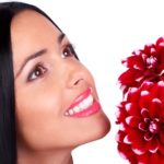 Smiling woman with  flowers. Over white background.